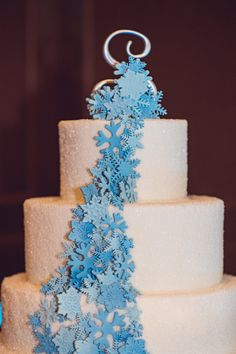 Ice blue fondant snowflakes cascading down three-tiered wedding cake covered in white sugar crystals at winter wonderland wedding | EOL Photography | villasiena.cc