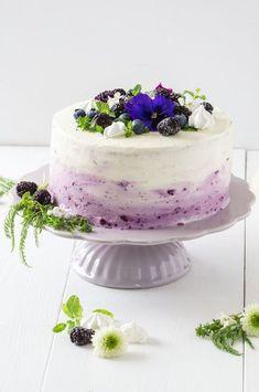 Lila Ombre Torte mit Heidelbeeren. Sehr saftige Torte mit fruchtiger Topfen/Quarkcreme und schönen Farbverlauf. Beeren und essbare Blüten als Dekoration.