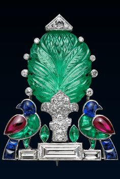 An Art Deco Birds and Tree Brooch, Cartier, 1925. Diamonds, emeralds, rubies and sapphires mounted in platinum. From the late 1920's Cartier was importing from India stones such as the carved emerald which gives an exotic charm to this design. #Cartier #ArtDeco #brooch