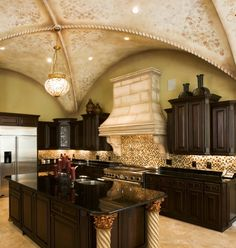 A luxurious kitchen on the farthest scale of a contemporary country kitchen. It sticks to a muted color palette of beiges and deep browns, but has accents of burgundy and gold. The carved pillars at one end of the spacious island are topped by ornate gilded carvings. The most impressive part of this kitchen is the barrel-vaulted, stenciled ceilings and the vintage light fixture hanging from the center.