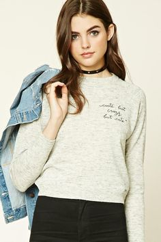 """A marled knit sweater featuring a """"Cute But Crazy But Cute"""" chest embroidery, a round neckline, long raglan sleeves, and ribbed trim."""
