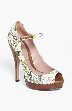 Lisbeth Pump  Gucci       Feathery florals paint the canvas of a darling peep-toe pump perched atop an earthy stacked heel and platform.