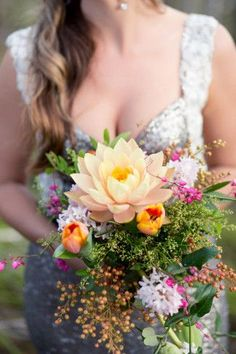 Breathtaking Wedding Bouquet: Spectacular cascading bouquet with a golden lotus flower, coral tulips, pink berries and pink blossoms. Click to blog for more gorgeous bouquet ideas.