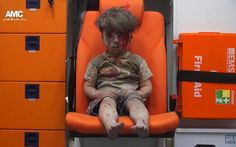 Five-year-old Omran Daqneesh sits in an ambulance after being pulled out of a building hit by an airstrike in Aleppo, Syria, on Aug. 17. / AP