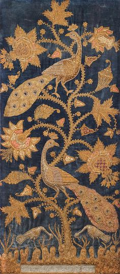 A metal thread-embroidered velvet Panel. Northern India, ca. 1900, blue velvet ground profusely embroidered with silver and gold thread with a flowering plant with two perching peacocks, beneath the plant a pool and two stalks