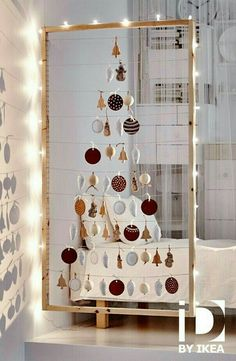 this ikea christmas tree is so great just a large wooden frame lined with christmas lights with ornaments strung on wires across it in the shape of a