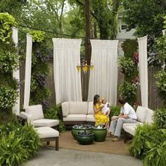 I love outdoor curtains!...Notice the plants grouped in the center, good alternative in the summer to a fire pit.