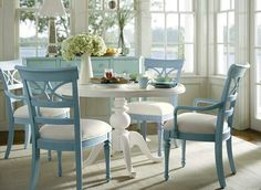 White table with blue chairs. Would be nice for a beach house or sun room.
