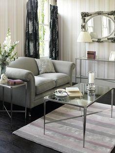 Salón con sofá gris y mesa de centro alta en cristal y metal