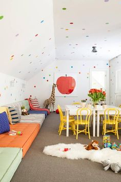 Under a sloped ceiling covered in colorful wall dots that continue down onto surrounding walls, this charming contemporary playroom is fitted with wall to wall colorful loungers lit by white cage sconces mounted facing a white play table surrounded by yellow Thonet Bentwood Chairs.