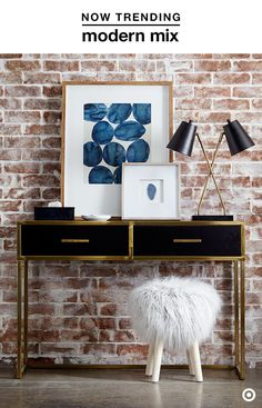 Glam up a hallway, entryway or living room with a modern look for fall. A console table serves as the foundation for the space, and sets the tone with black finish and brass trim—Plus, those drawers are perfect for storing odds & ends. Bring in a bold pop of color with a framed print in rich blue hues. A black and brass table lamp is the perfect complement to the table, and adds ambiance. Finish the look with a piece that really makes a statement and adds extra seating, like a faux-fur…