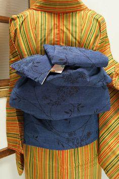 濃紺と淡藍の糸で織りなされた野の花のようなアラベスクがロマンチックな正絹紬地の兵児帯です。