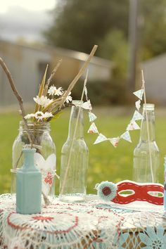 Love this mini bunting in old bottles...