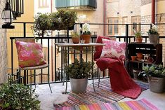 Soak up early spring sunshine with a colorful iron wrought balcony! Multi-print pillows and area rugs add a cheerful splash of color. #apartment #patio #pink