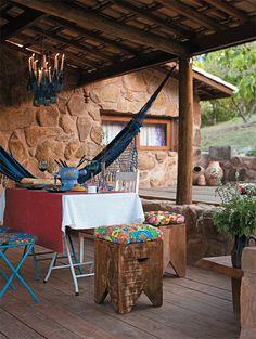 O clima informal e caprichado fica completo com a cobertura de telhas vãs (aparentes) de barro e o castiçal de garrafas de vidro