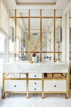 The gleaming master bath in this Paris pied-à-terre, covered floor to ceiling in luxe layers of statuary marble, mirror, and brass | archdigest.com