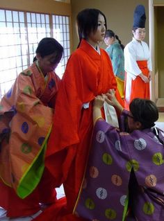Women being dressed in junihitoe land kariginu layer by layer.
