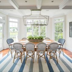 This coastal dining area features a Darlana Linear Chandelier from Visual Comfort and bistro chairs from Serena & Lily | Design № Five
