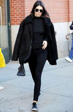 Kendall Jenner wears a black top, fur-lined jacket, leggings, and Nike sneakers