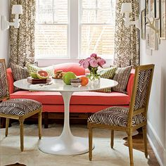 Modern Twist | A Saarinen-inspired table adds mid-century drama to this sunny dining nook. The bold coral fabric gives a jolt of energy to the classic camelback sofa, and a zigzag print livens up the upholstered chairs.