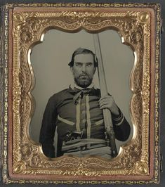 Unidentified Confederate soldier wearing popular style battleshirt similar to those worn by Quantrill soldiers/ bushwhackers. Holding double barrel percussion shotgun and cocked Colt Navy revolver.