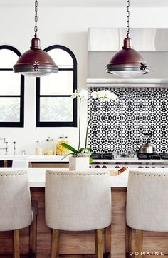 Black and white backsplash in kitchen with brass, industrial lights over kitchen island and orchid