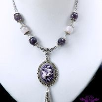 Because of my love for gemstones as well as cameos, I really enjoyed creating this piece! This approximately 19 inch antique silver plated necklace has been adorned with faceted beads in genuine natural amethyst and rose quartz capped in silver plated filigree. An ornate scroll style connector di...