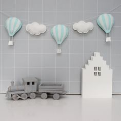 A modern, handmade, felt garland of hot air balloons and clouds, a perfect accessory for the nursery or children's bedroom. This item is intended as a decor ite