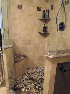 Tiled shower with dark brown river rock floor and corner seat - love!