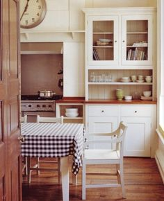 Country Kitchen. Simplicity, blue and white checkered tablecloth, white cabinets w/ two pottery bowls.