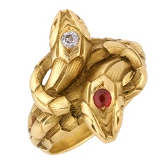 The crossover ring designed as two entwined snakes, the heads set with a circular-cut ruby and circular-cut diamond respectively, within a mount realistically carved with scales, 1900s, numbered 1633. French assay marks for gold. Size 20. weight 10.86g. Via Barbara Alexander.