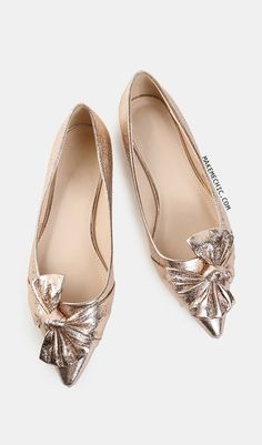 Metallic Bow Pointy Flats ROSE GOLD.    Add a touch of glimmer to your ensemble with the Metallic Bow Pointy Flats! Features a metallic PU upper, pointed toe, statement bow design, and a flat heel. Complete the look with a high slit maxi skirt and a bralette.