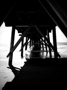 Fishing pier in Topsail Island, North Carolina at low tide in monochrome.