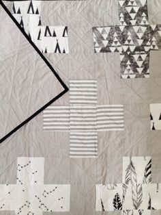 this beautiful modern quilt is made up with plus signs from our exclusive Miss j. fabrics across the top and a one color grey on the back, hand bound in true black for a perfectly clean edge.  www.missjhandmade.com