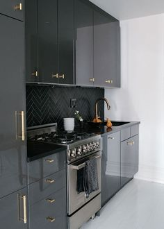 a bachelor in brooklyn. Black Lacquered  cabinets and herringbone backsplash topped off with brass hardware