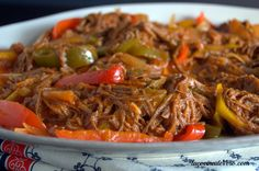 "Ropa Vieja (Shredded Flank Steak Stew) Ropa vieja means ""old clothes,"" which the meat resembles when it is shredded. Although this dish is typically known as a Cuban dish each of the spanish speaking caribbean islands has their own version of Ropa Vieja. Meat Recipes, Slow Cooker Recipes, Mexican Food Recipes, Crockpot Recipes, Cooking Recipes, Healthy Recipes, Ethnic Recipes, Mexican Dishes, Healthy Desserts"