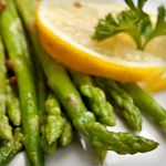 Heat grill to medium-high.   Toss asparagus with oil, salt and pepper. Place asparagus crosswise on the grill and