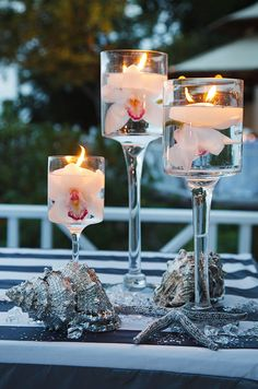 Glass vases of floating candles and white orchids hover over silver shells for a luxurious, oceanic feel.