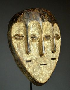 Africa |Triple face mask from the Lega or Lengola people of DR Congo. Wood, white kaolin, encursted patina |ca. early to mid 20th century