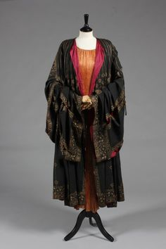 A fine and rare Mariano Fortuny stencilled orientalist black silk evening coat, circa 1910-20, with circular label applied to the wine silk lining, stencilled in gold with delicate foliate traceries with vines and grapes, the wide panelled sleeves and skirts linked by striped glass Murano beads, tie cords to neck - See more at: http://kerrytaylorauctions.com/archive-list/?id=63&sts=archive&paging=3#sthash.lpY8u3lB.dpuf