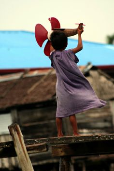 Girl playing with her toy airplane inTawi-Tawi, Mindanao, Philippines