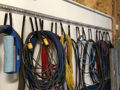 This is a great way to store extension cords and hoses. Screw a piece of perforated steel angle to the wall and use rubber bungee cords to hang coiled items. Easy to access and do not get tangled together.
