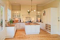 custom made provincial kitchen with handpainted profile doors, timber benchtops and glass display cabinets