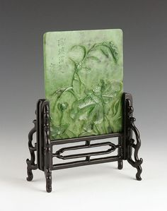"Table screen, China, carved spinach jade, with floral design and poem inscribed on front, on wood stand, jade 6"" h x 5 1/2"" w, overall 9 1/4"" h x 6 1/4"" w. 10/15000"