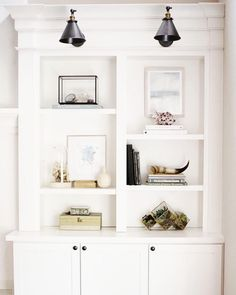 Bookcase behind fridge with armed lights above