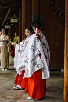 Two Miko in traditional dress form part of a wedding procession at Meiji Shrine in Tokyo, Japan