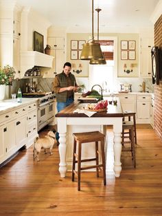 LOVE LOVE LOVE the old fashioned look of the flooring and Island/seats. Whitewashed cabinetry, marble countertops, and a generous island make this southern kitchen functional and charming. Don't forget to accessorize the walls of your kitchen as you would your dining room―a mantel-like oven hood is a great place to start. (Photo: Laurey W. Glenn)