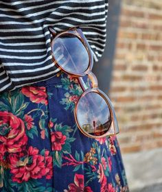 Have those sunnies. Round sunglasses, floral skirt, striped top.
