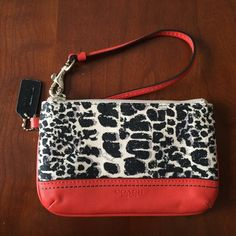 "NWOT Authentic Coach wristlet Ocelot print and red/orange leather detailed Coach wristlet. Never used. Interior has two pockets to fit cards. Measures 6.5"" by 4.5"" Best in Bags and Work Week Chic Host Pick Coach Bags Clutches & Wristlets"