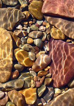 sun shining through water onto rocks